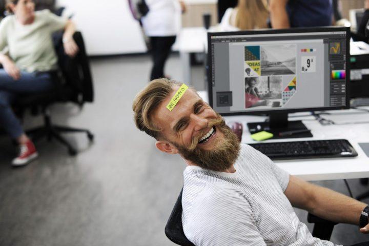 Facet z brodą przy kompie tworzy grafikę